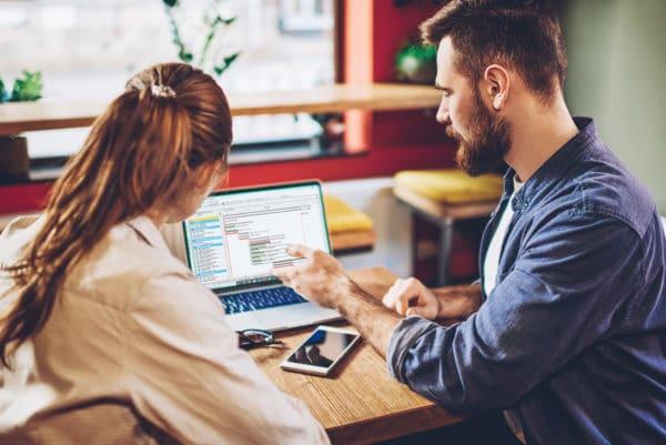 twee collega's met laptop overleg over risico's